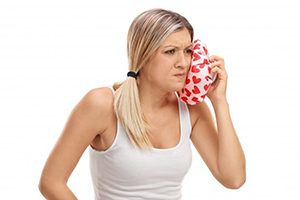 woman in white tank top holding cold compress to her face